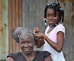 A girl braids her mother's hair in Batey Bombita, a community in the southwest of the Dominican Republic whose population is composed of Haitian immigrants and their descendents.