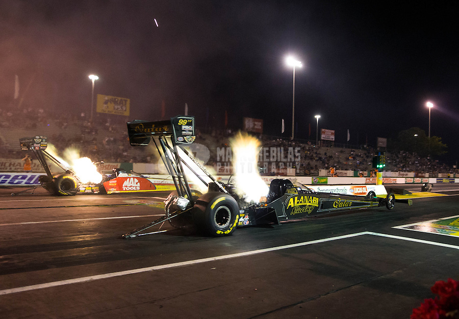 May 30, 2014; Englishtown, NJ, USA; NHRA top fuel driver Khalid Albalooshi (near lane) races alongside Doug Kalitta during qualifying for the Summernationals at Raceway Park. Mandatory Credit: Mark J. Rebilas-