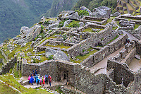 Peru, Machu Picchu.  Early Morning Light Rain Falling.  Tourists in Multicolored Ponchos About to Enter the Main Doorway into the City.