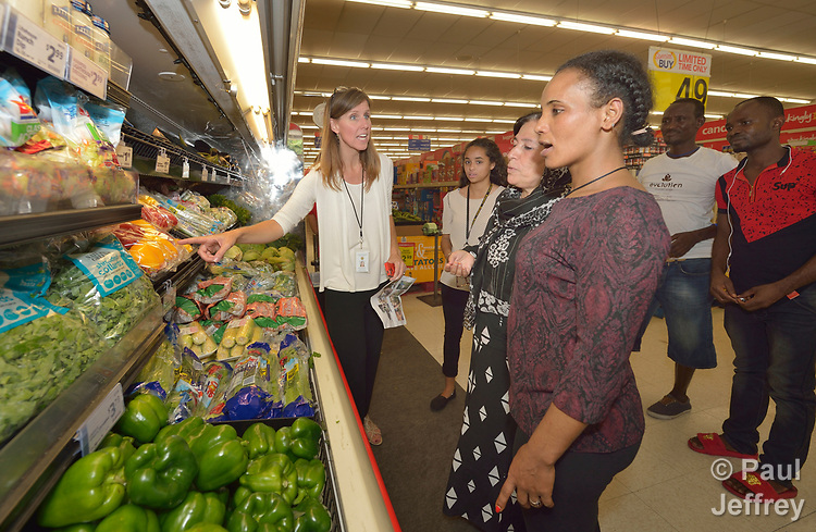 Penny Gushiken (left) leads a cultural orientation class for newly arrived refugees in Lancaster, Pennsylvania. During a visit to a supermarket, participants discuss available food items, including fresh produce. The class is sponsored by Church World Service. <br /> <br /> Photo by Paul Jeffrey for Church World Service.