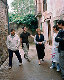 SPAIN, Ezcaray, La Rioja, family standing in alley amid buildings