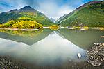 Chugach Mountains in fall colors reflect on  Valdez Glacier Lake, Valdez, Southcentral Alaska, Autumn.