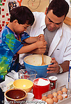 4 year old boy with father, in kitchen, cooking baking vertical stirring batter with wooden spoon