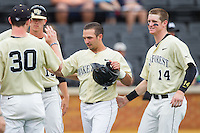 Joey Rodriguez (7) of the Wake Forest Demon Deacons is congratulated by teammates Conor Keniry (14) and Connor Johnstone (30) after hitting a solo home run against the Virginia Cavaliers at Wake Forest Baseball Park on May 17, 2014 in Winston-Salem, North Carolina.  The Demon Deacons defeated the Cavaliers 4-3.  (Brian Westerholt/Four Seam Images)