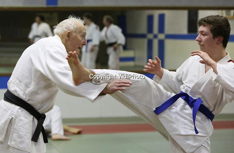Foto: VidiPhoto..DOESBURG - De 90-jarige Wim van Delden uit Doetinchem traint donderdag in zijn Doesburgse sportschool. Van Delden is met stip de meest fitte hoogbejaarde van Nederland en tevens de enige actieve vechtsporter van die leeftijd. De drager van de zwarte band heeft de tweede dan jiujitsu en zet zijn arm- en beenklemmen nog als een jonge vent, vertelt zijn Sensei. Tweemaal in de week .traint de ninja opa bij Sport- en Recreatie-instituut Doesburg met sporters die tientallen jaren jonger zijn. Alleen zijn conditie blijft wat achter bij de rest. Foto: Wim van Delden traint met de 17-jarige Fosz Tijsma uit Doesburg..