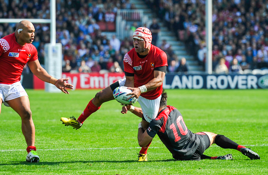 Tonga's Will Helu off loads the ball despite the tackle from Georgia's Lasha Malaguradze<br /> <br /> Photographer Craig Thomas/CameraSport<br /> <br /> Rugby Union - 2015 Rugby World Cup - 12;00  Georgia v Tonga - Saturday 19th September 2015 - Kingsholm - Gloucester <br /> <br /> &copy; CameraSport - 43 Linden Ave. Countesthorpe. Leicester. England. LE8 5PG - Tel: +44 (0) 116 277 4147 - admin@camerasport.com - www.camerasport.com