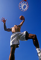 Basketball player goes in for a lay-up.
