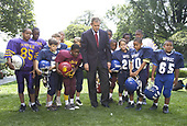 (SECOND OF TWO PHOTOS) United States President George W. Bush, surrounded by Washington, D.C.-area Pop Warner League players in the White House Rose Garden, Sunday, September 9, 2001, watches his coin toss to decide which teams would kickoff games on opening day of the National Football League's regular season. The coin landed tails side up. <br /> Mandatory Credit: Tina Hager / White House via CNP