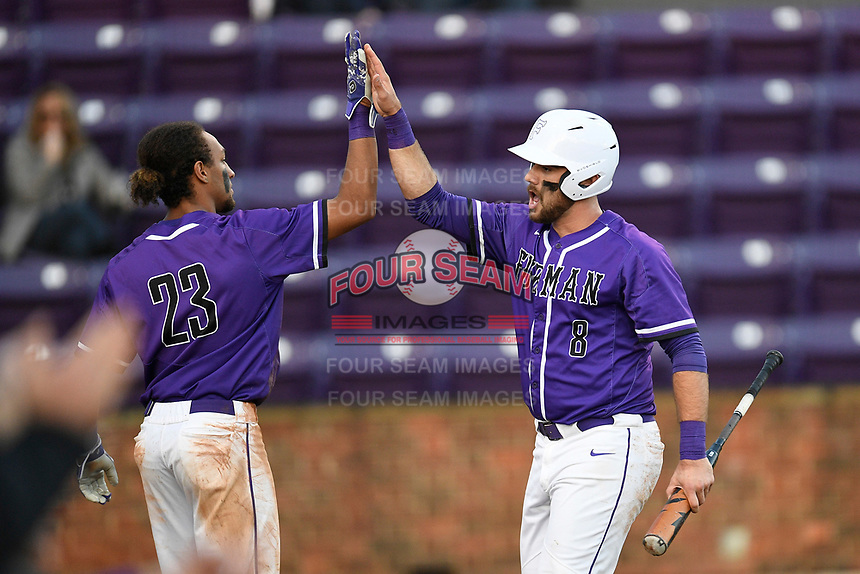 John Michael Boswell (8) of the Furman Paladins is congratulated by Jordan Starkes after scoring a run in a game against the UNC Asheville Bulldogs on Wednesday, February 27, 2019, at Latham Baseball Stadium on the Furman University campus in Greenville, South Carolina. UNC Asheville won, 4-3. (Tom Priddy/Four Seam Images)