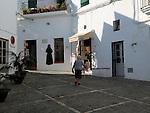 Woman walking in cobbled street whitewashed buildings in Vejer de la Frontera, Cadiz Province, Spain