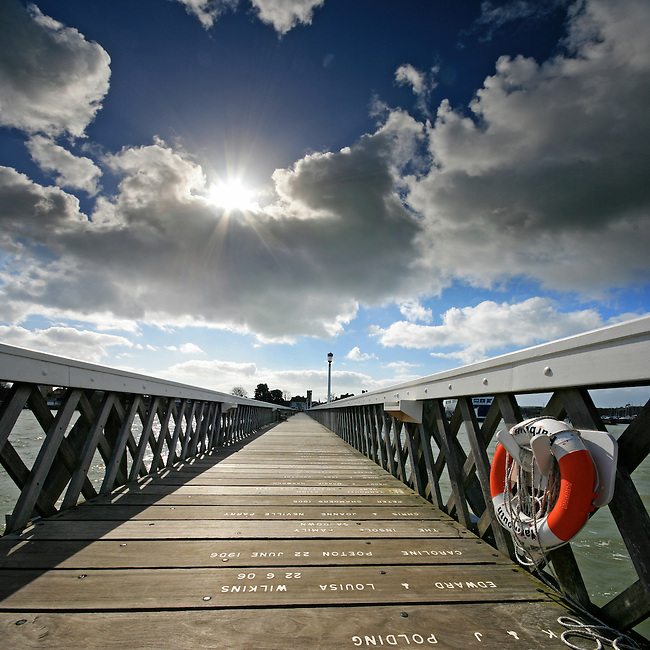 The wide-angle lens and low point-of-view helps to create a dramatic vanishing point looking back towards the town from Yarmouth Pier on the Isle of Wight.<br />