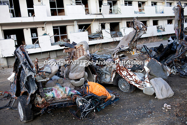 OTSHUSHI, JAPAN - DECEMBER 5: Destroyed cars are seen outside a destroyed and deserted apartment building on December 5, 2011, in Otshushi, Japan. The small town was almost wiped off the map during the tsunami and only a supermarket and Buddhist temple remain standing in the center of the town. Northeastern Japan's coastline was struck by an earthquake measuring 9.0 on the Richter scale and a Tsunami on March 11, 2011 which destroyed villages and livelihoods for hundreds of thousands of people. Almost 16,000 dead, thousands missing, more than 700,000 properties destroyed and an estimated 387,000 survivors lost their homes. Its estimated that it will take more than five years to rebuild. The cost is estimated to 309 billion U.S. dollars, the world's most expensive natural disaster. Many children suffered especially with school destroyed, education interrupted and the loss of family members took a heavy toll. (Photo by Per-Anders Pettersson)