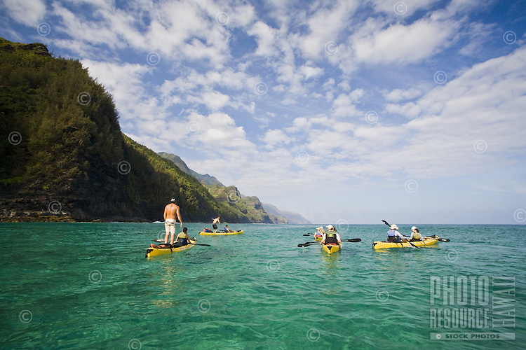 People paddling kayaks in the clear blue waters of the Na Pali Coast (kayak, kayaker)