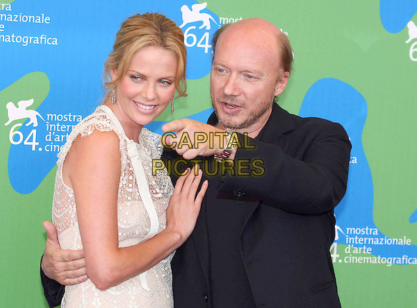 "CHARLIZE THERON & PAUL HAGGIS.Attend the ""In the valley of Elah"" photocall in Venice during day 4 of the 64th Venice International Film Festival, Italy, 1st  September 2007..La Biennale di Venezia half length black shirt cream white lace hand pointing.CAP/OME.©Luca Ghidoni/Omega/Capital Pictures."