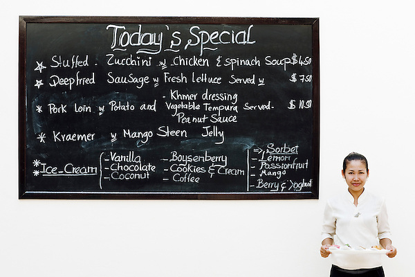 Waitress stands by chalkboard featuring the day's specials at FCC Angkor Kitchen, FCC Angkor hotel, Siem Reap, Cambodia. The Kitchen is a casual dining venue at FCC Angkor hotel with 250 seats and an East-West menu.