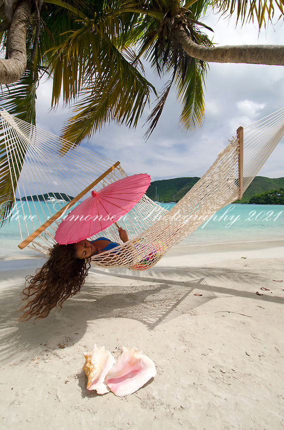 Aldris Santana in a hammock with a pink parasol and conch shells<br /> Maho Bay, St. John<br /> Virgin Islands National Park