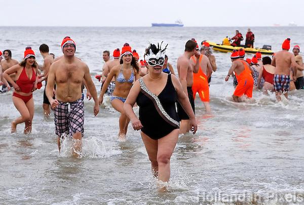 Traditionele Nieuwjaarsduik in Scheveningen. Mensen rennen de zee uit