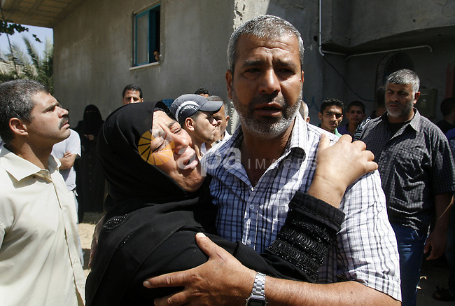 The mother of Palestinian militant Ahmed Abu Nasser, 20, is comforted by relatives as she mourns during his funeral in Khan Yunis in the southern Gaza Strip on June 2, 2012. An Israeli soldier and two Palestinian militants, including Abu Nasser, were killed in a Palestinian attack and a retaliatory air strike, sources on both sides said. Photo by Eyad Al Baba