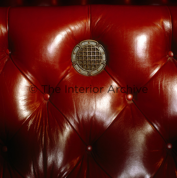 Detail of a brass porthole which conceals a speaker in one of the upholstered benches in the Chamber
