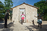 Iznaida Dalmas, 7, jumps rope in front of her family's new house on the Haitian island of La Gonave. Her siblings Vestander and Erm hold the rope. Service Chrétien d'Haïti is working with survivors of Hurricane Matthew, which struck the region in 2016, to rebuild damaged housing. A member of the ACT Alliance, SCH also supports agriculture on the island by providing tools, seeds, and technical support and training for farmers.