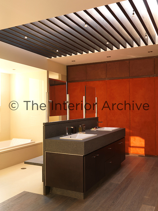Wooden slats over the skylight diffuse the light in this spacious and modern bathroom