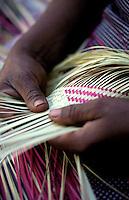 Hands making basket out reeds.