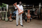 ACCRA, GHANA - JUNE 13: Happy Ideall, the founder of Unique Ceramics Center, holds a Vase in his factory on June 13, 2008 in central Accra, Ghana. He hopes to increase his domestic and export business by working with Herman Chinery-Hesse, a local software entrepreneur, who is pioneering to bringing e-commerce to remote corners of the continent. (Photo by Per-Anders Pettersson)....