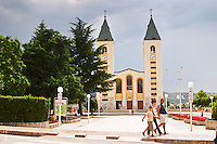 The church with its twin church towers. A family walking in front of the church. Medugorje pilgrimage village, near Mostar. Medjugorje. Federation Bosne i Hercegovine. Bosnia Herzegovina, Europe.