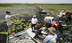 "Wayne ""Hoho"" Brooks, left, talks with Harry Dutton, center, the statewide alligator managment coordinator with the Florida Wildlife Commission as the 6 airboats gather in the middle of Lake Miccosukee to take a break and eat while the helicopter goes to refuel July 19, 2007.  The 14 men from both the Florida Wildlife Commission and private commercial alligator farms collected 562 eggs at Lake Miccosukee 25 miles east of Tallahassee, Florida."