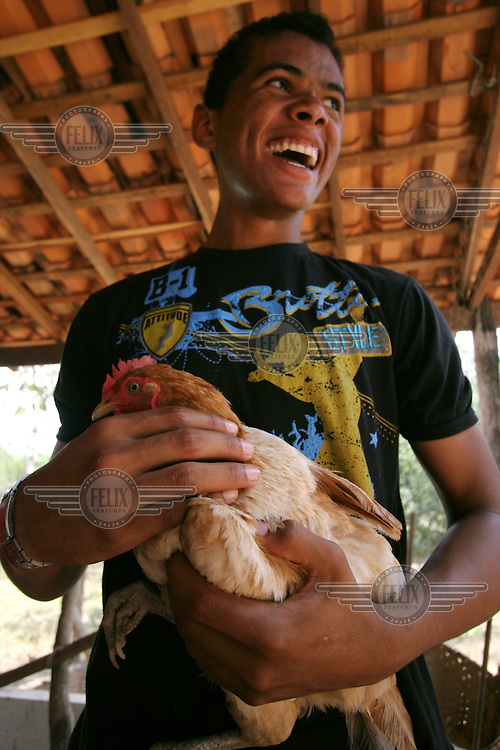 A student at the Escola Familia Agricola Antonio Fontenele (EFA) near Lago do Junco, holds a chicken on the school farm. Students, many who come from far away, alternate living at the school and at home for 14 days at a time. The school is supported by the Association of Land Reform Settlements of Maranhao State (ASSEMA), an umbrella NGO of associations operated for and by rural peasants and Babacu nut breakers.