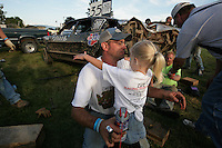 Kali Faith VanDalen hugs her dad Shane VanDalen behind the scenes of the Demolition Derby. Van Dalen owns the NY Life car behind him. They live in Lynden. Photo by Meryl Schenker ..