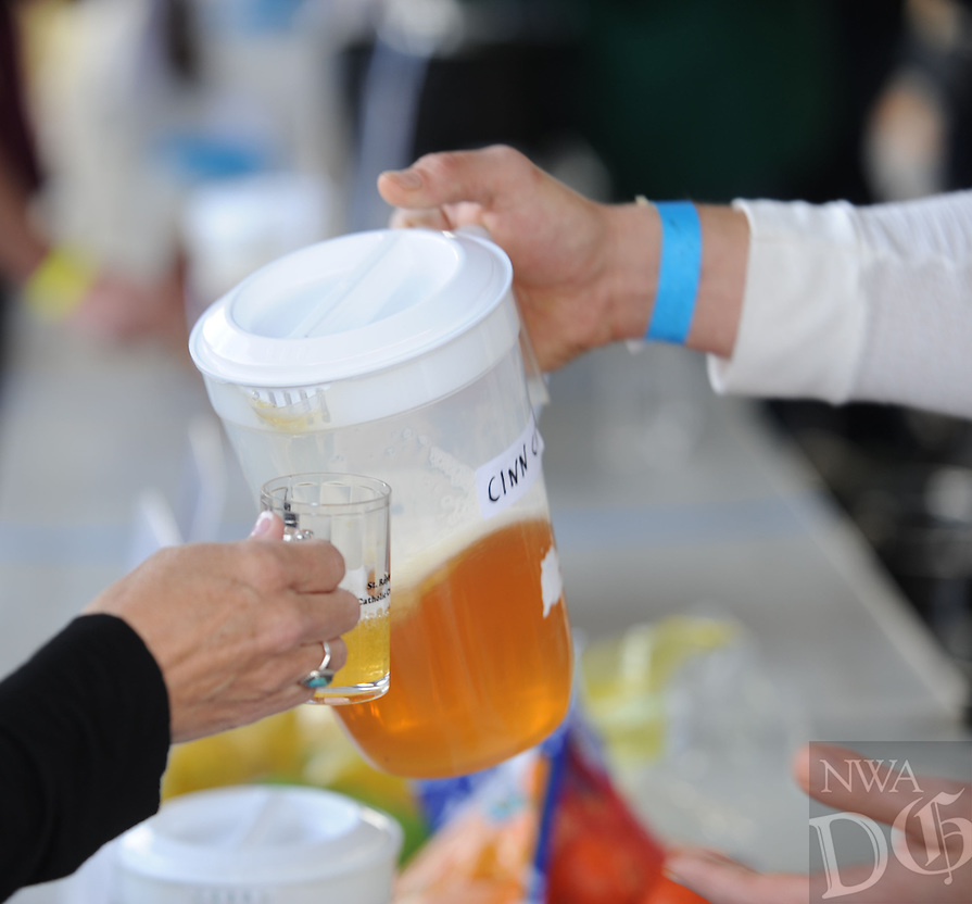 NWA Democrat-Gazette/ANDY SHUPE<br /> A visitor receives a sample Saturday, Oct. 17, 2015, of Pappy's Hard Cider during the second St. Raphael Catholic Church Brewtober Chilifest in Springdale. The event gave attendees the chance to taste home-brewed beers and ciders and sample chili with awards going to the two winners as determined by a popular vote.