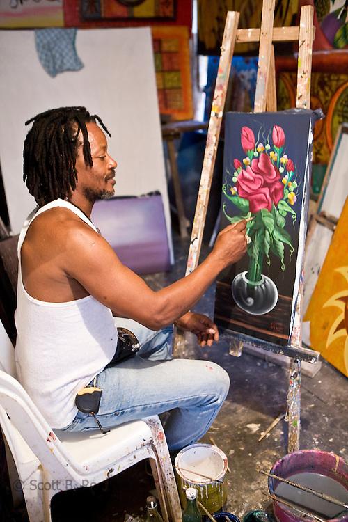 Haitian man paints in his studio in Las Terranas, Dominican Republic