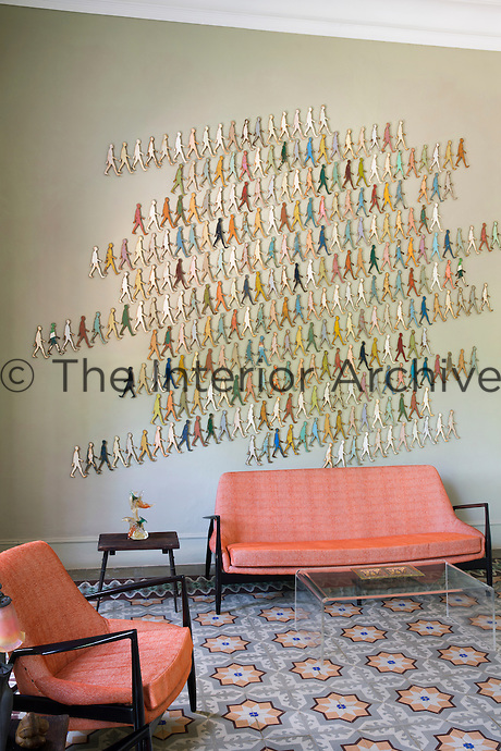 """One wall of this living room is covered in small metal cut outs of human figures, part of a series by Damian Aquiles called """"Infinite Time, Infinite Colour and Infinite Memory"""""""