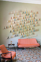 "One wall of this living room is covered in small metal cut outs of human figures, part of a series by Damian Aquiles called ""Infinite Time, Infinite Colour and Infinite Memory"""