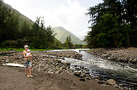 A young mother and toddler son stand near a rocky stream at the mouth of Waipi'o River (where it enters the ocean), Waipi'o Valley, Hamakua District, Big Island; another visitor wades through the stream in the distance.