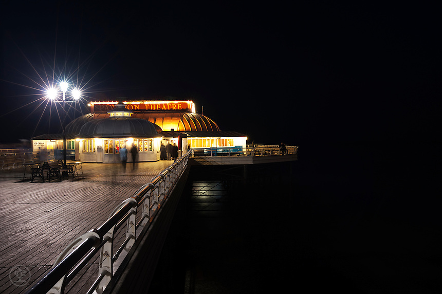 The Pavilion Theatre lit up after dark on Cromer Pier, Norfolk.