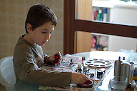 Ten year old boy painting figurines in the kitchen, France.