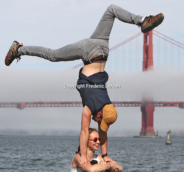 French tourist do a unique pose in front of San Francisco's Golden Gate Bridge.