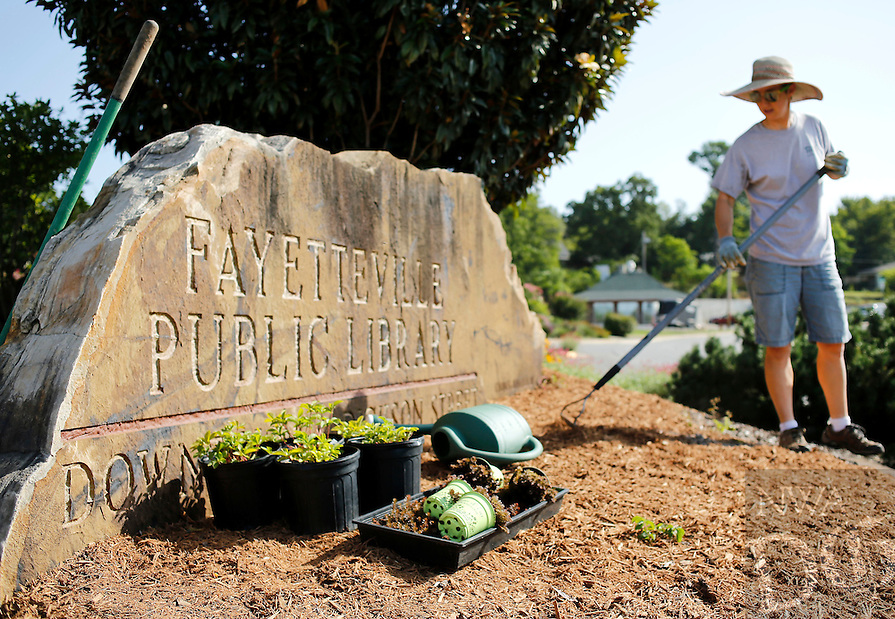 NWA Media/DAVID GOTTSCHALK - 8/20/14 - Jenifer (cq) Royer, a horticulturist with the city of Fayetteville Parks and Recreation Department, prepares the grounds near the intersection of Prairie Street and School Avenue Wednesday August 20, 2014. Royer was working with Roxanne Worthy, not pictured, also a horticulturist with the city of Fayetteville Parks and Recreation Department, on the street scape where they are adding mulch and planting Sedum and Potentilla.
