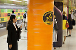 A woman takes a picture of a column displaying a giant carrot in the Tokyo Metro passageway in Shinjuku on September 1, 2015, Tokyo, Japan. The Central Union of Agricultural Co-operatives (JA-ZENCHU) is promoting Japanese vegetables with the vegetable columns and a massive 80 meter ''Wall Farmer's Market'' information poster until September 6th. (Photo by Rodrigo Reyes Marin/AFLO)