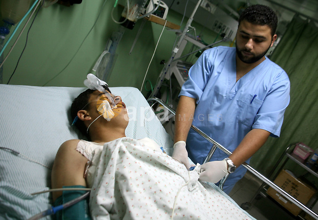 A medic adjusts the bed of a wounded Palestinian youth at a hospital in Beit Lahia in the northern of Gaza Strip on August 24, 2009. One Palestinian man was killed and another wounded by Israeli gunfire on the northern edge of the Gaza Strip, Gaza medics reported, as an Israeli military spokeswoman said two rockets or mortar rounds had been fired towards southern Israel, without reporting any casualties. Neither man was known to be a member of any militant faction, the medics added.  Mohammed Othman