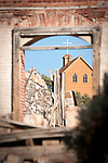 Church on the hill framed through arch of abandoned building ruins