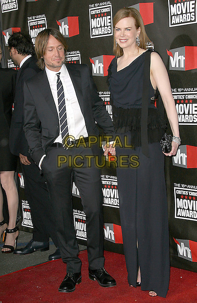 KEITH URBAN & NICOLE KIDMAN .at The16th Annual Critics' Choice Movie Awards held at The Hollywood Palladium in Hollywood, California, USA, January 14th, 2011..full length black navy blue dress tiered sleeveless  ruffles ruffle long maxi open toe shoes slit split clutch bag holding hands tall short suit tie husband wife couple .CAP/RKE/DVS.©DVS/RockinExposures/Capital Pictures.