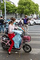 Suzhou, Jiangsu, China.  Young Woman on Motorbike with Breathing Mask.