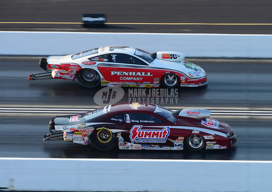 Jul. 1, 2012; Joliet, IL, USA: NHRA pro stock driver Greg Anderson (near lane) races alongside Mike Edwards during the Route 66 Nationals at Route 66 Raceway. Mandatory Credit: Mark J. Rebilas-