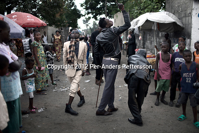"""KINSHASA, DEMOCRATIC REPUBLIC OF CONGO - FEBRUARY 12: Sapeurs entertain locals in the Mombele area on February 12, 2012 in Kinshasa, DRC. The word Sapeur comes from SAPE, a French acronym for Société des Ambianceurs et Persons Élégants or Society of Revellers and Elegant People and it also means, to dress with elegance and style"""". Most of the young Sapeurs are unemployed, poor and live in harsh conditions in Kinshasa,  a city of about 10 million people. For many of them being a Sapeur means they can escape their daily struggles and dress like fashionable Europeans. Many hustle to build up their expensive collections. Most Sapeurs could never afford to visit Paris, and usually relatives send or bring clothes back to Kinshasa. (Photo by Per-Anders Pettersson)"""