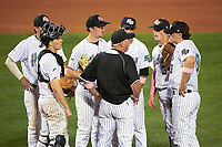 Stetson Hatters Pete Dunn (jacket) talks with his team, including third baseman Colton Lightner (4), catcher Austin Hale (18), starting pitcher Adam Schaly (50), shortstop Matt Morales (7), second baseman Jack Machonis, and first baseman Will Mackenzie (9) during a game against the Siena Saints on February 23, 2016 at Melching Field at Conrad Park in DeLand, Florida.  Stetson defeated Siena 5-3.  (Mike Janes/Four Seam Images)