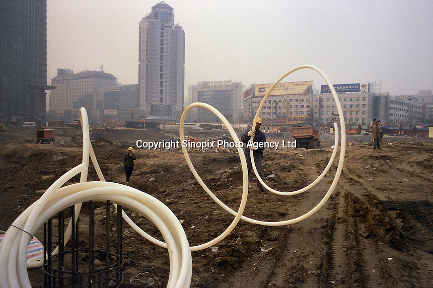 Migrant labor from Henan Province at work on a downtown construction site, in a pollution haze that closed the airport in Beijing, China. The site was formerly occupied by hutong housing..15 May 2007