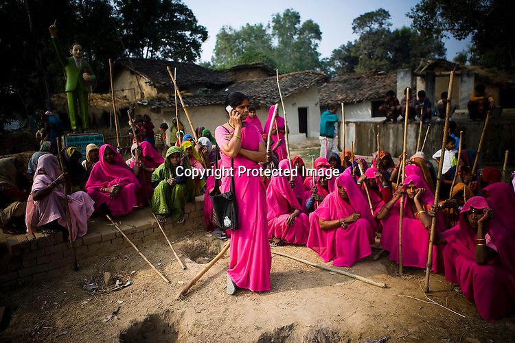 The 47-year-old leader of the Pink Gang, Sampat Pal Devi (centre) is a fiesty woman. The barely educated, impoverished mother of five, Sampat Pal Devi has emerged as a messianic figure in the region. Sampath Devi began to work as a government health worker, but she quit soon after because her job was not satisfying enough. She always wanted to work for the poor and not for herself. Taking up issues while being a government worker was difficult, so she decided to quit the job and work for the rights of people...Amidst the gloom of extreme poverty, it's the colour of pink that's calling the shots in this dusty region of Bundelkhand, one of the poorest parts of one of India's northern and most populous states, Uttar Pradesh in India. A gang of vigilantes, called the Gulabi Gang (pink gang) - its 10,000 strong women members wear only pink sarees - is taking up lathi (traditional Indian cudgel) against domestic violence and corruption.